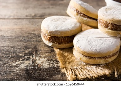 Traditional Argentinian alfajores with dulce de leche and sugar on wooden table. Copy space