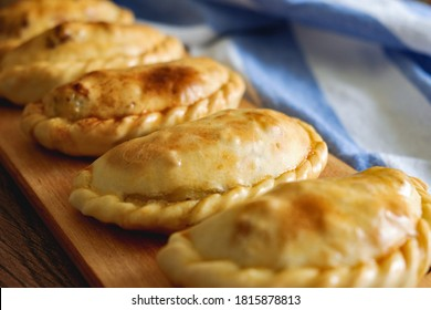 Traditional Argentinian baked empanadas on a wooden plate