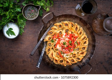 Traditional Armenian manti with mincemeat and paprika tomato salad as top view in a cast iron pan