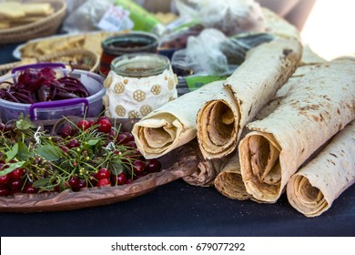 Traditional Armenian pita bread (lavash) and red cherry on a table with traditional food during Mulberry festival in Karahunj village, Armenia
