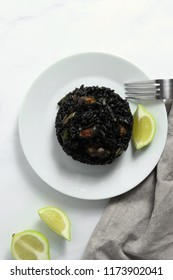 Traditional arroz negro - arròs negre - black rice dish, typical for Valencia, on white marble surface