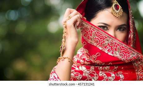 Traditional asia beautiful woman in sari national costume covered her face with veil, India