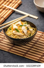 Traditional asian or chinese noodles with chicken and vegetablesin black plate and wood chopsticks on dark stone table