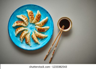 Traditional asian dumplings Gyozas on turqoise ceramic hand painted plate served with chopsticks and bowl of soy sauce over grey texture background. Top view with copy space.