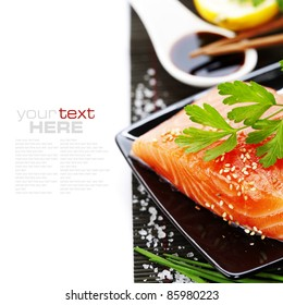 traditional asian ingredients (Fresh salmon steak filet, lemon and soy sause) with chopsticks over white with sample text