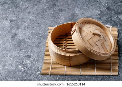 Traditional asian kitchen utensil bamboo steamer over blue texture background. Top view, flat lay. Copy space