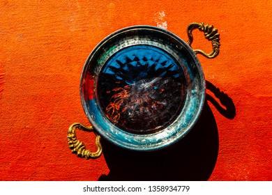 Traditional asian metal bowl for Menemen scrambled egg, sunny red background.
