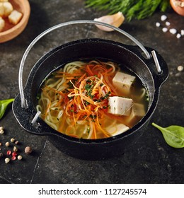 Traditional Asian Soup with Noodles and Chicken in Metal Bowler on Dark Background. Vietnamese Pho Ga Soup or Japanese Miso Soup with Protein Cubes of Poultry Meat or Tofu
