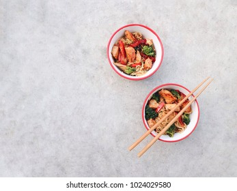 Traditional Asian wok noodles in a colorful bowls. Noodles with chicken and vegetables, chopsticks on a concrete stone background. Tasty Chinese/Thai dinner. Fast food concept. Space for text.