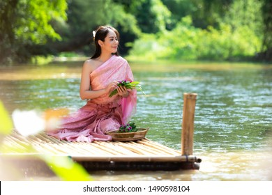 Traditional asian woman Thai dress sitting and relax in wood bridge nature river.  Thailand