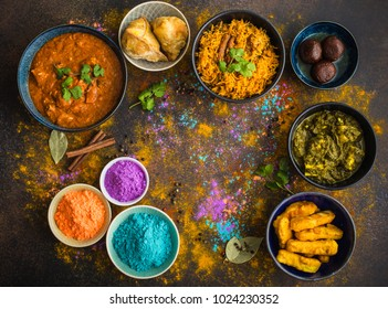 Traditional assorted Indian food, Holi colours powder, rustic background. Indian Holi holiday. Indian dishes and snacks set. Holi celebration. Top view. Festive Indian table setting. Space for text