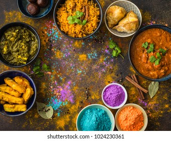 Traditional assorted Indian food, Holi colours powder, rustic background. Indian Holi holiday. Indian dishes and snacks set. Celebration. Top view. Festive Indian table setting. Space for text
