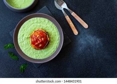 Traditional Australian dish called Pie Floater. Green pea soup served with Australian meat pie. Australian cuisine. Black background. Top view. Copy space