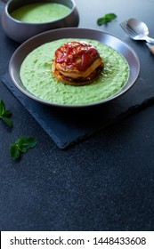 Traditional Australian dish called Pie Floater. Green pea soup served with Australian meat pie. Australian cuisine. Black background. Close-up. Copy space