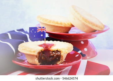 Traditional Australian Meat Pies for Australia or Anzac Day holiday party food, in red, white and blue setting, with applied faded retro style filters.