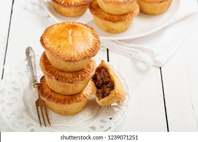 Traditional Australian Mini meat pies from shortbread dough on a white wooden background.