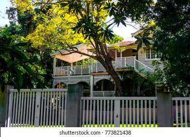 Traditional Australian Queenslander House with tropical foliage and wood and stairs