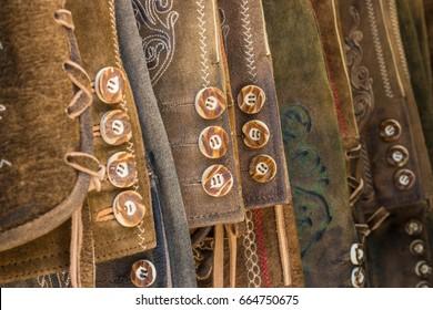 Traditional austrian and bavarian lederhosen (leather pants). Various lederhosen hanging in a row. Closeup of buttons.