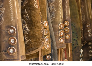 Traditional austrian and bavarian lederhosen (leather pants). Various lederhosen hanging in a row. Closeup of buttons.