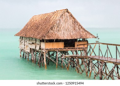 Traditional authentic over water thatched roof bungalow of native local aborigines Micronesian people in lagoon of South Tarawa atoll under heavy rain shower, wet season, Kiribati, Micronesia, Oceania