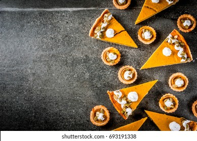 Traditional autumn dishes. Halloween, Thanksgiving. Set of spicy pumpkin pie and pumpkin tartlets with whipped cream & pumpkin seeds on black stone table. Copy space top view