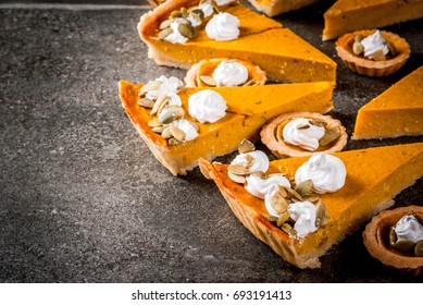 Traditional autumn dishes. Halloween, Thanksgiving. Set of spicy pumpkin pie and pumpkin tartlets with whipped cream & pumpkin seeds on black stone table. Copy space
