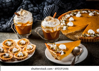 Traditional autumn dishes. Halloween, Thanksgiving. Spicy pumpkin pie, pumpkin tartlets with whipped cream & pumpkin seeds, pumpkin latte with cinnamon on black stone table with blanket. Copy space