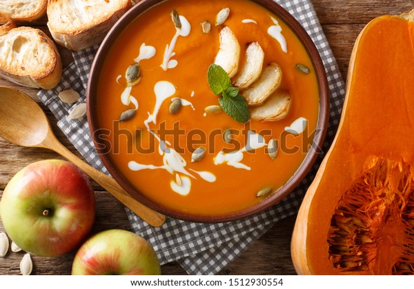 Traditional autumn pumpkin and apple soup with seeds close-up in a bowl on the table. Horizontal top view from above