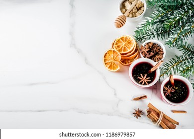 Traditional autumn winter hot homemade cocktail, red mulled wine drink with ingredients, white marble background copy space