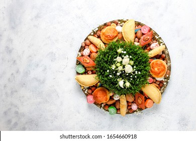 Traditional Azerbaijan holiday Novruz background with xoncha,green semeni,traditional azerbaijan sweets,shekerbura,qogal,paxlava,mutaki and different nuts and sweets,top view,space for copy