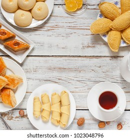 Traditional Azerbaijan holiday Novruz cookies baklava on white plate on the white background with nuts and shakarbura,gogal,sweetbread,tea,lemon,kata,mutaki,flat lay,top view,space for copy