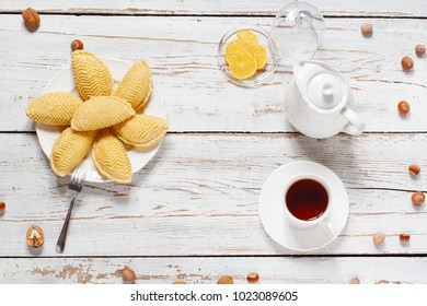 Traditional Azerbaijan holiday Novruz cookies on white plate on the white background with nuts and shakarbura,tea,lemon,flat lay,top view,space for copy