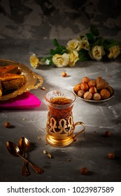 Traditional Azerbaijan holiday Novruz cookies baklava and hazelnuts and nuts background with cup of tea armudu glass
