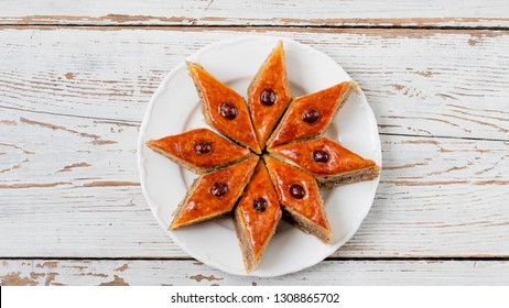Traditional Azerbaijan holiday Novruz cookies baklava on white plate on the white background with nuts and shakarbura,tea,lemon,kata,mutaki,flat lay,top view,space for copy