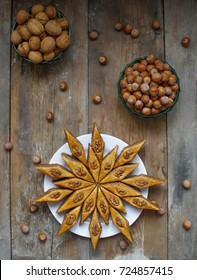 Traditional Azerbaijan holiday Nowruz cookies baklava on white plate on the rustic background with nuts and huzelnuts on green plate ,flat lay