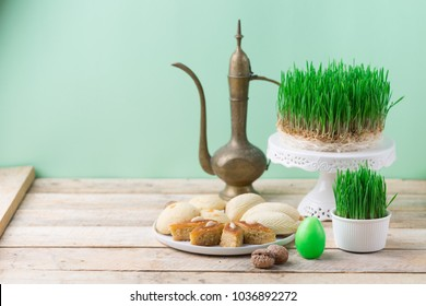 Traditional Azerbaijan Novruz table decoration setting for spring equinox new year celebration, white plate with shekerbura and pakhlava, vintage jar wheat grass symbol Nowruz, close up copy space