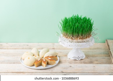 Traditional Azerbaijan pastries shekerbura and pakhlava for Novruz spring equinox celebration, white plate wooden table with green fresh wheat grass symbol, Persian Nowruz sabzi, close up copy space