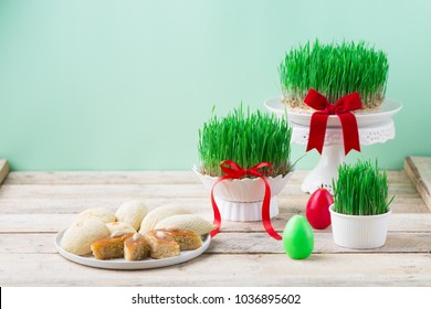 Traditional Azerbaijan pastries shekerbura and pakhlava for Novruz spring equinox celebration in white plate wooden table decoration with green semeni fresh wheat grass symbol with red ribbon tied bow