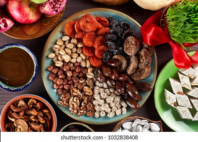Traditional Azerbaijan sweet cuisine of holiday Nowruz: national dessert called Sumalak, lavash bread, halva, assortment of nuts and dry fruits. Sprouted seeds with red ribbon. Fresh green grass