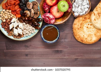 Traditional Azerbaijan sweet cuisine of holiday Nowruz: national dessert called Sumalak, lavash bread, halwa, assortment of nuts and dry fruits. Top view, copy space