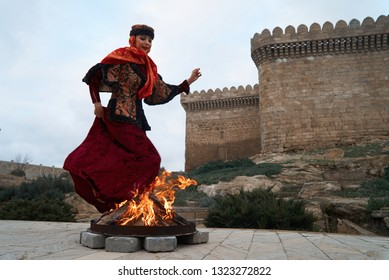Traditional Azerbaijani Novruz holiday celebration with beautiful girl Jumping over the fire, outdoors