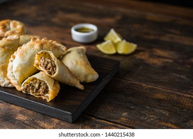 Traditional baked Argentine empanadas savoury pastries with meat beef stuffing against wooden background