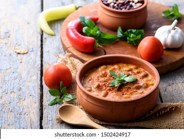 Traditional baked beans in tomato sauce cooked in retro clay pot with spices and vegetables. Homemade healthy cuisine.