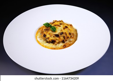 Traditional baked julienne with mushrooms, cheese and bechamel sauce on a white plate with black background. Baked chicken with mushrooms, cheese and sauce.