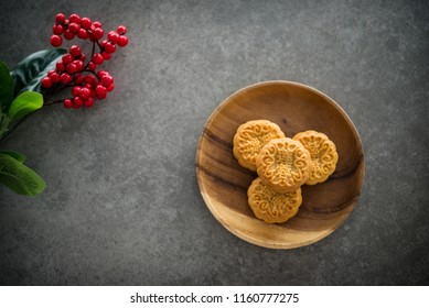 "Traditional baked mooncakes is offered to friends or family during Mid-Autumn Festival. Flatlay on table top down view dark background with copy space. The Chinese character  represent ""lotus paste"""