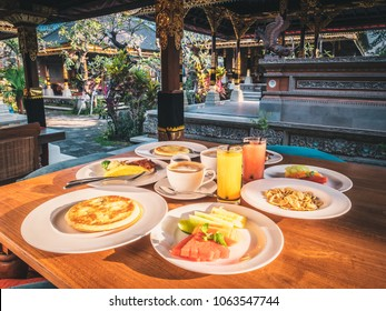 Traditional Balinese breakfast at sunny morning on honeymoon holidays. Fresh fruits and pancakes with orange and melon juice.