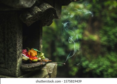 Traditional balinese Canang Sari offerings to gods and spirits with flowers, food and smoky aromatic sticks on dark green background. Indonesian culture and religion. Bali authentic travel concept.
