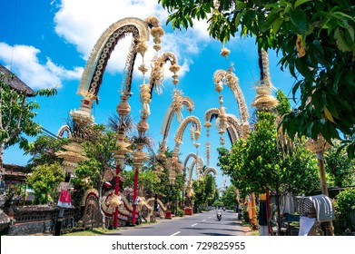 Traditional balinese penjors along the street of Bali, Indonesia. Tall bamboo poles with decoration are set in honour of hindu gods on religious festivals like Galungal, Kuningan.
