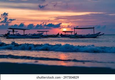 traditional Balinese ships Jukung close on Sanur beach at sunrise, Bali, Indonesia