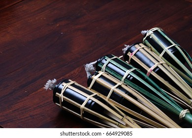 Traditional bamboo lamp torch for decoration over dark wood background. Selective focus.